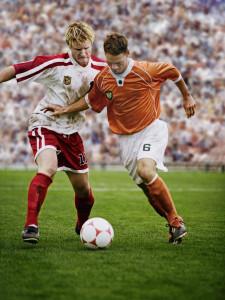 Rival Soccer Players Kicking Ball