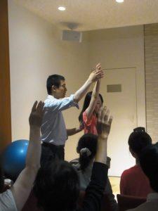 生徒さんが腕を下ろし始めるときに、肩甲骨や腕の付け根を押し下げないように指導中のアレクサンダーテクニークの教師かわかみひろひこ