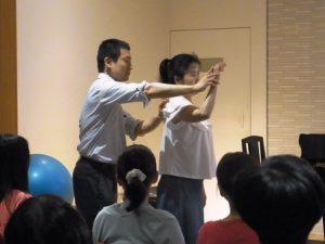 持ち上げた腕を下ろすときには、肘や指先に降り始めてから、少し遅れてから肩甲骨が降りるように指導中のアレクサンダ-テクニークの教師かわかみひろひこ