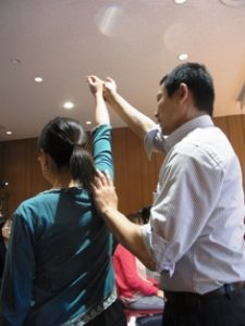 生徒さんが腕を持ち上げるときに、頭を胴体に押し下げないように、背中側とくに肩甲骨周辺を押し下げないように指導中のアレクサンダーテクニークの教師かわかみひろひこ