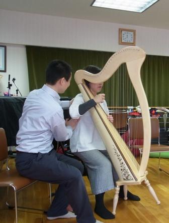 アイリッシュハープ奏者に、脇の下を押し下げることを防止するディレクションを指導中のアレクサンダーテクニーク教師かわかみひろひこ